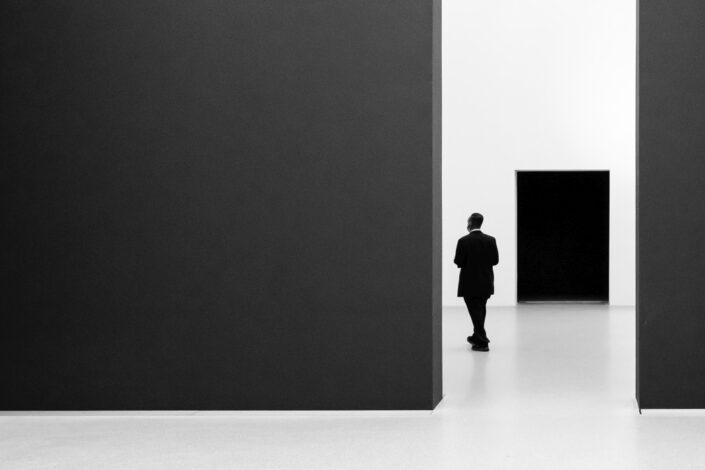 black man between black rectangles indoor street photography moment