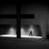 street photography of a building with a huge cross and a man walking in artificial light