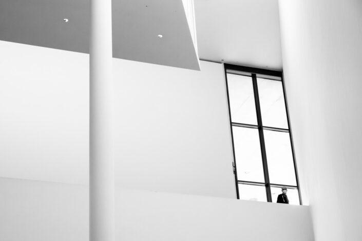 photograph of a man standing inside a huge modern window in a geometric building
