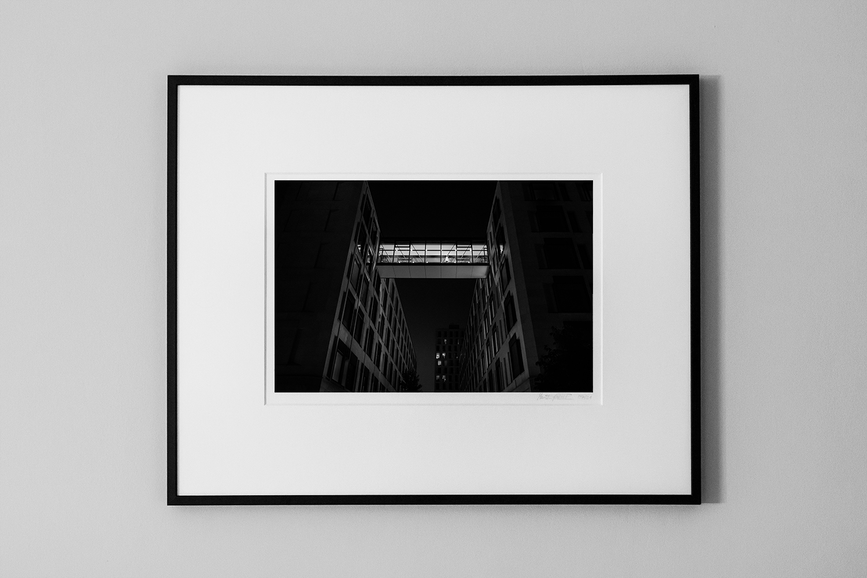 fine art print of a illuminated bridge between two skyscrapers at night