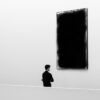 modern minimalist photograph of a man in black thinking about the art in front of him