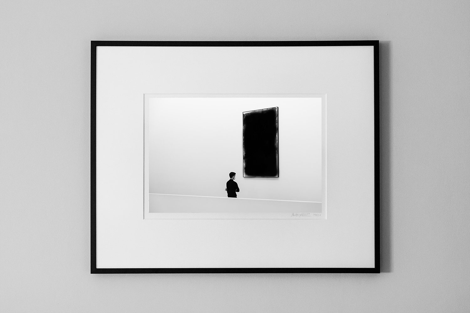 minimalist photograph of a man in black thinking about the art in front of him