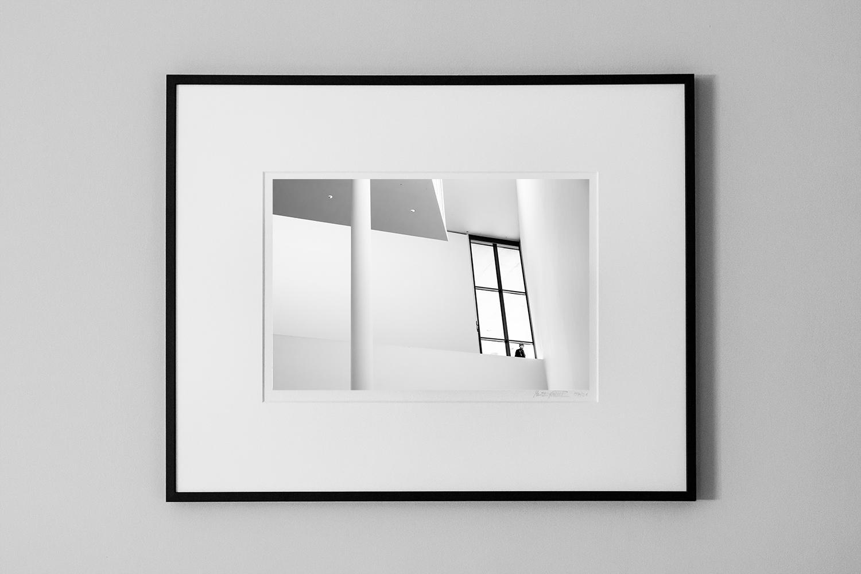 photograph of a man standing inside a huge modern window